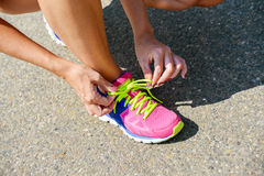 Fit woman binding her sports shoes Royalty Free Stock Images
