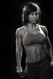Female athlete. Monochrome portrait of attractive female athlete dressed in sports bra and shorts standing while holding weights in both hands royalty free stock photos