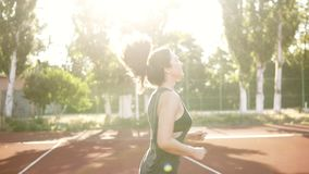 Fit woman in black sport bra and shirt running outdoors. Brunette girl with pony tail happilly jogging. Sunlight