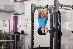 Bodybuilding. Strong fit woman exercising in a gym - doing pull-ups. Stock Image