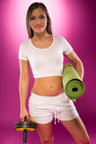 Fit woman carrying exercise equipment Stock Image