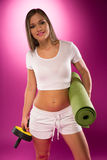 Fit woman carrying exercise equipment Royalty Free Stock Image