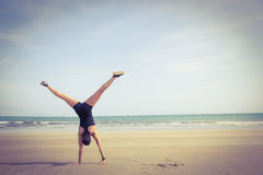 Fit woman cartwheeling on the sand Royalty Free Stock Images
