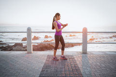 Fit woman checking smart watch at promenade Stock Photography