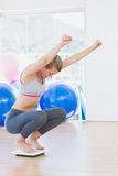 Fit woman cheering on scale in exercise room Stock Image