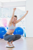 Fit woman cheering on scale in exercise room Royalty Free Stock Photo