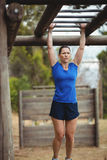 Fit woman climbing monkey bars. In bootcamp Royalty Free Stock Photos