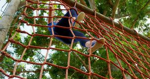 Fit woman climbing a net during obstacle course 4k. Fit woman climbing a net during obstacle course in boot camp 4k stock video footage