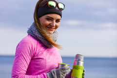Fit woman in cold day warming up drink tea Royalty Free Stock Images