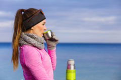 Fit woman in cold day warming up drink tea Stock Photography