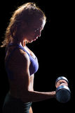 Fit woman concentrating while exercising with dumbbell. Against black background royalty free stock image