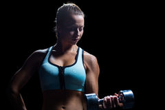 Fit woman concentrating while lifting dumbbell Royalty Free Stock Photo