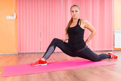 Fit Woman in a Deep Lunge Stretch on a Mat Royalty Free Stock Photography