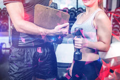 Fit woman discussing performance with trainer. At gym Royalty Free Stock Photography