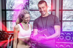 Fit woman discussing performance with trainer. At gym Stock Photos
