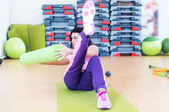 Fit woman doing abs workout exercise russian twists with raised leg.  royalty free stock photography