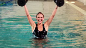 Fit woman doing aqua aerobics in the pool with foam dumbbells stock footage