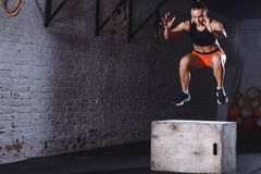 Fit woman doing box jump exercise. Muscular woman doing box jumps at gym. Fit young woman doing box jump exercise. Muscular woman doing box jumps at gym stock photos