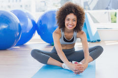 Fit woman doing the butterfly stretch in exercise room Stock Image