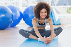 Fit woman doing the butterfly stretch in exercise room Royalty Free Stock Photo