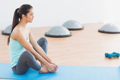Fit woman doing butterfly stretch in exercise room Royalty Free Stock Photos
