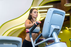 Fit woman doing cardio in an elliptical trainer in a gym. Royalty Free Stock Photos
