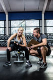 Fit woman doing dumbbells exercise with trainer. Fit women doing dumbbells exercise with trainer at gym Royalty Free Stock Photos