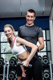Fit woman doing dumbbells exercise with trainer. Fit women doing dumbbells exercise with trainer at gym Royalty Free Stock Photo