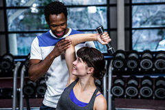 Fit woman doing dumbbells exercise with trainer. Fit women doing dumbbells exercise with trainer at gym Royalty Free Stock Images