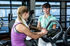 Fit woman doing exercise bike with trainer stock image