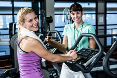 Fit woman doing exercise bike with trainer Royalty Free Stock Photography