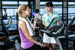 Fit woman doing exercise bike with trainer Stock Photography