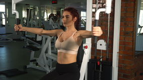 Fit woman doing exercise on chest. Machine in gym stock footage