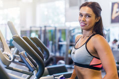Fit woman doing exercise on a elliptical trainer. Stock Photo
