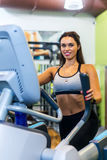 Fit woman doing exercise on a elliptical trainer. Stock Images