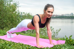 Fit woman doing full plank core exercise fitness training working out outdoors.  royalty free stock photography