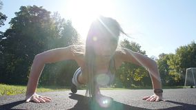 Fit woman doing full plank core exercise fitness training working out outdoors. Push up. Fit woman doing full plank core exercise fitness training working out stock video footage