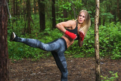 Fit woman doing kickboxing training, exercising, working out outdoors stock image