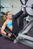 Fit woman doing leg presses in gym Royalty Free Stock Photo