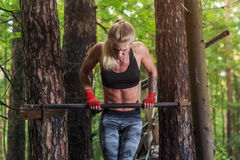Fit woman doing muscle up on horizontal bar.  Stock Image