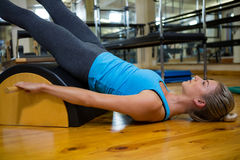Fit woman doing pilates on arc barrel. In fitness studio Stock Photos