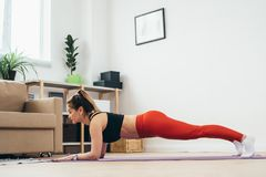 Fit woman doing plank exercise at home. Royalty Free Stock Images