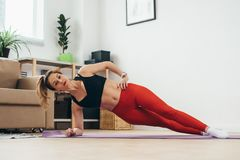 Fit woman doing plank exercise at home. Stock Photos