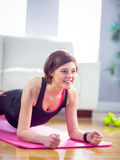 Fit woman doing plank on mat Stock Photography