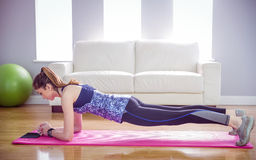 Fit woman doing plank on mat. At home in the living room stock photo
