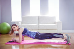 Fit woman doing plank on mat. At home in the living room royalty free stock image
