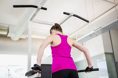 Fit woman doing pull up. At the gym stock photo