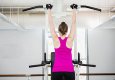 Fit woman doing pull up. At the gym Stock Image
