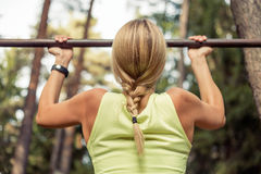Fit woman doing pull-ups Stock Image