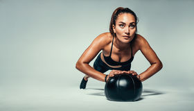 Fit woman doing push up on medicine ball. Horizontal shot of young fit woman doing push up on medicine ball. Fitness female exercising with a medicine ball on Royalty Free Stock Photos